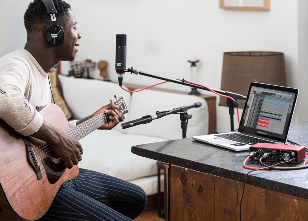 Man playing guitar and singing while using Scarlett 2i2